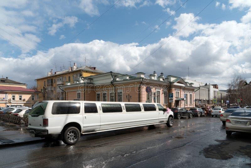 Το άσπρο limousine πολυτέλειας περιμένει τα newlyweds στην αλέα στο υπόβαθρο της Βουλής των οικογενειακών εορτασμών μετά από στοκ φωτογραφίες