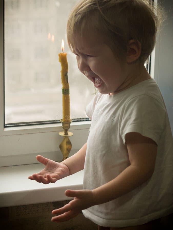 Το άτακτο μικρό παιδί άγγιξε την πυρκαγιά κεριών στοκ εικόνα με δικαίωμα ελεύθερης χρήσης