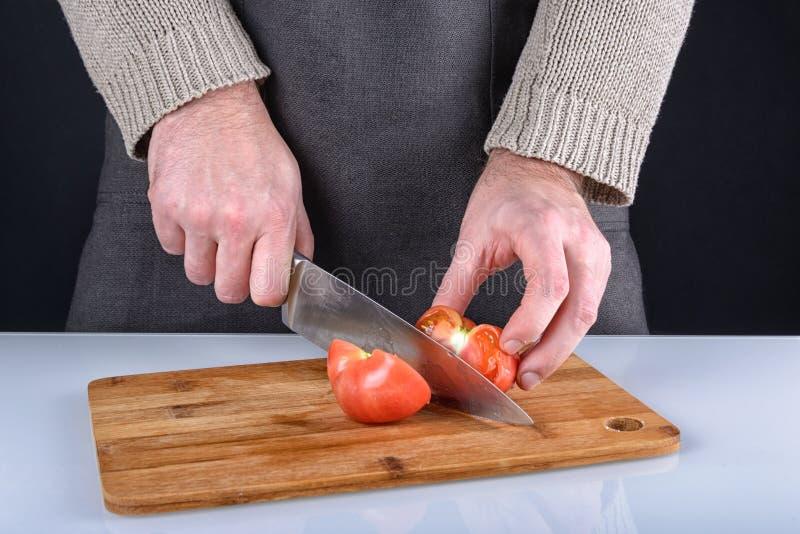 Το άτομο έκοψε μια ντομάτα σε δύο μισά με ένα μαχαίρι Μια όμορφη φωτογραφία της διαδικασίας μαγειρέματος στοκ φωτογραφία