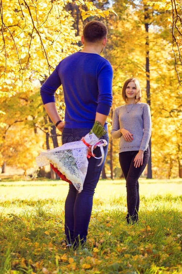 Το άτομο έκρυψε μια ανθοδέσμη των τριαντάφυλλων στοκ εικόνες