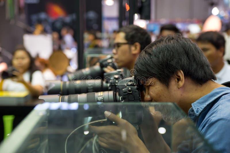 Το άτομο δένει έξω μια κάμερα Nikon στοκ φωτογραφίες