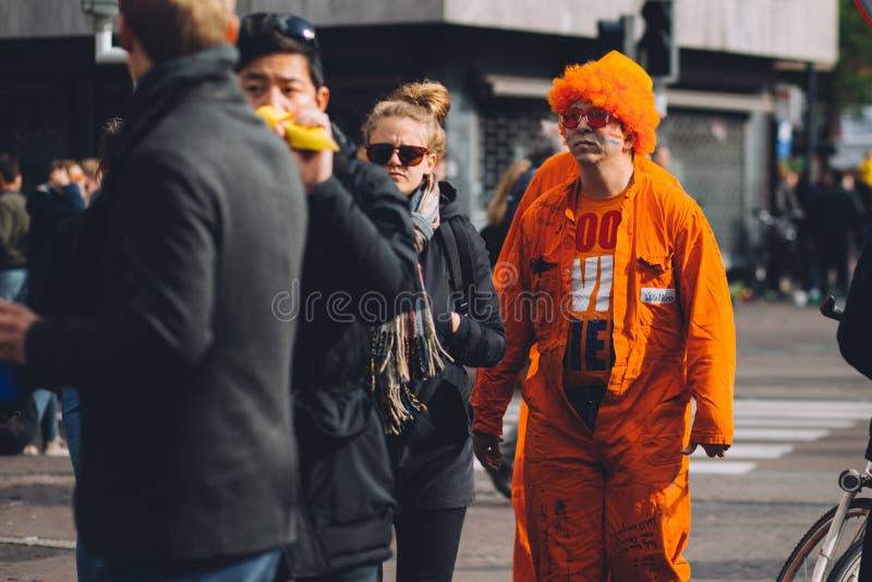 Το άτομο έντυσε στην πορτοκαλιά, τρελλή περούκα, εορτασμός ημέρας βασιλιάδων ` s