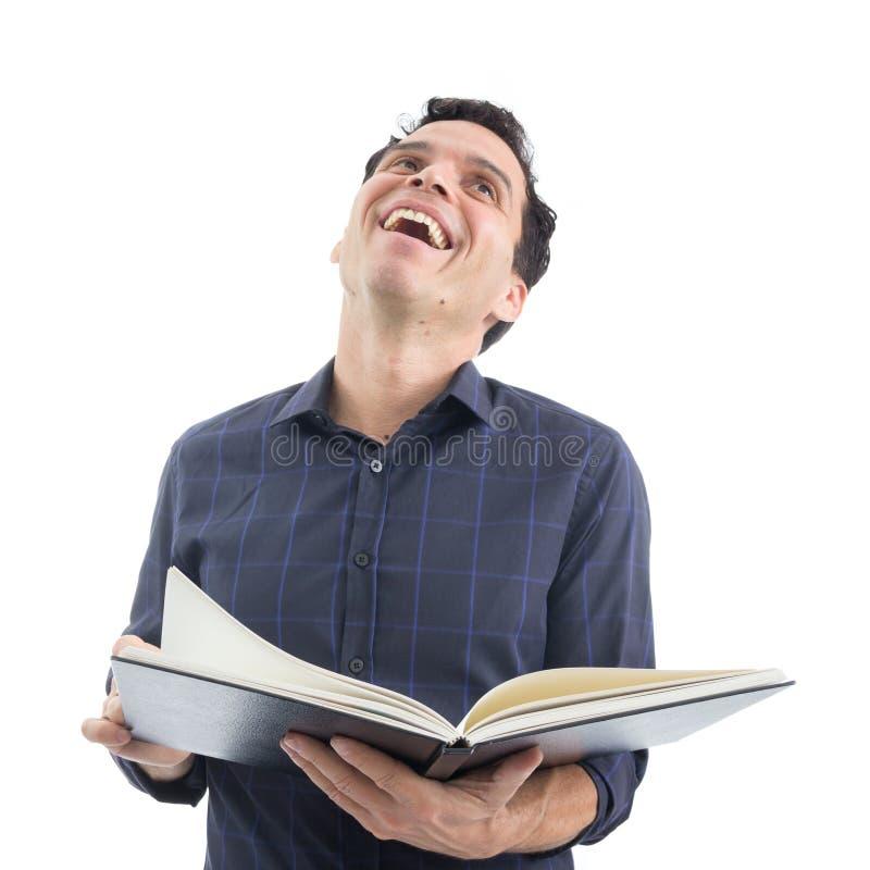 Το άτομο έχει τη διασκέδαση διαβάζοντας το βιβλίο Το πρόσωπο φορά σκούρο μπλε έτσι στοκ φωτογραφίες