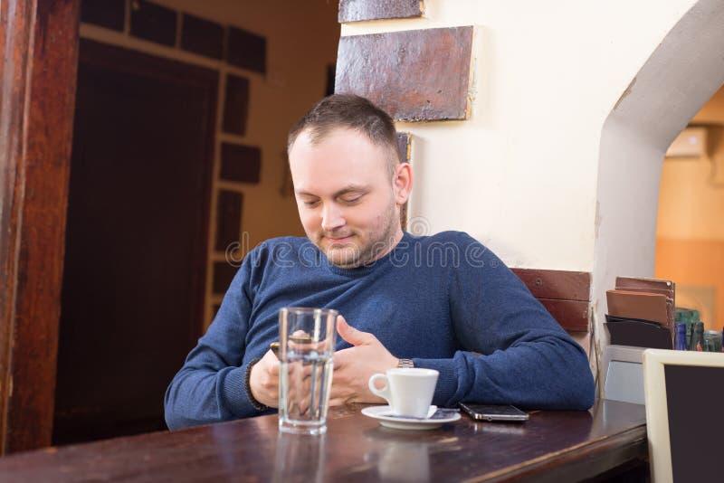 Το άτομο έχει τον καφέ σε μια συνεδρίαση φραγμών και κοιτάζει στο τηλέφωνό του στοκ εικόνα με δικαίωμα ελεύθερης χρήσης