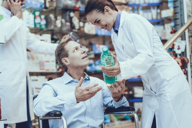 Το άτομο αγοράζει ένα μεταλλικό νερό στο φαρμακείο στοκ εικόνα με δικαίωμα ελεύθερης χρήσης