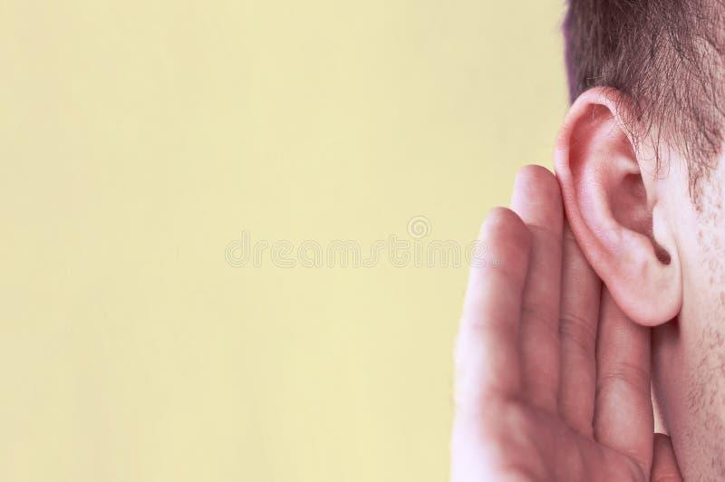 Το άτομο ακούει προσεκτικά με το φοίνικά της το αυτί της, κλείνει επάνω, έννοια ειδήσεων στοκ εικόνες