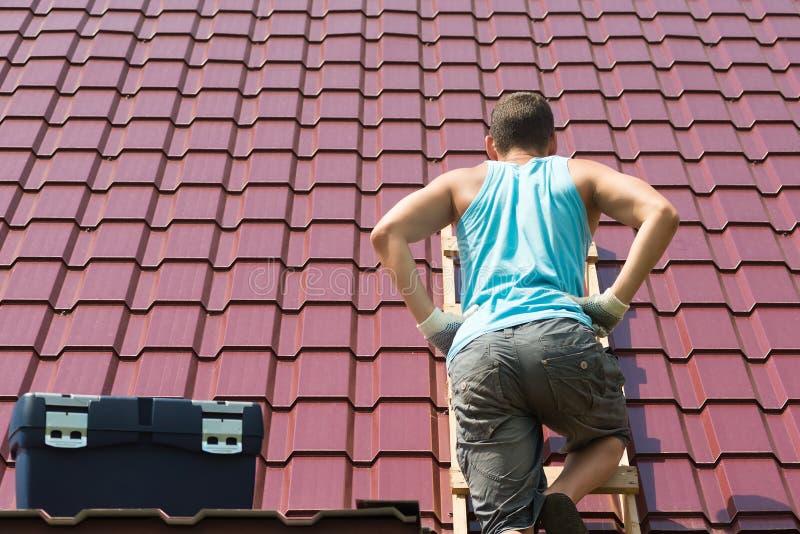 Το άτομο αναρριχήθηκε επάνω στη στέγη του σπιτιού με τα εργαλεία για να το επισκευάσει στοκ εικόνες