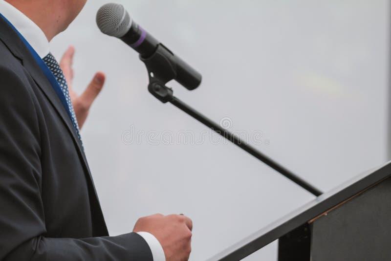 Το άτομο αποδίδει στη διάσκεψη - μιλά στο μικρόφωνο για το ακροατήριο στοκ φωτογραφία με δικαίωμα ελεύθερης χρήσης
