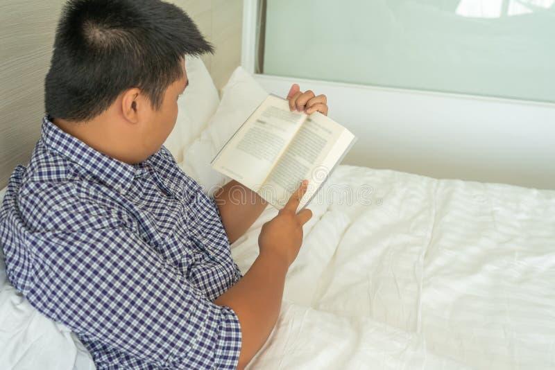 Το άτομο απολαμβάνει το καλό βιβλίο στο κρεβάτι πριν από το χρόνο ύπνου στοκ φωτογραφία με δικαίωμα ελεύθερης χρήσης