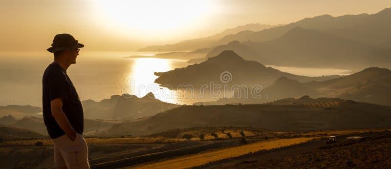 Το άτομο απολαμβάνει τη θέα της θάλασσας και montains στο χρόνο ηλιοβασιλέματος στοκ εικόνες