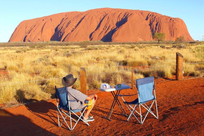 Το άτομο απολαμβάνει το θεαματικό ηλιοβασίλεμα του βράχου Uluru Ayers στοκ εικόνα με δικαίωμα ελεύθερης χρήσης