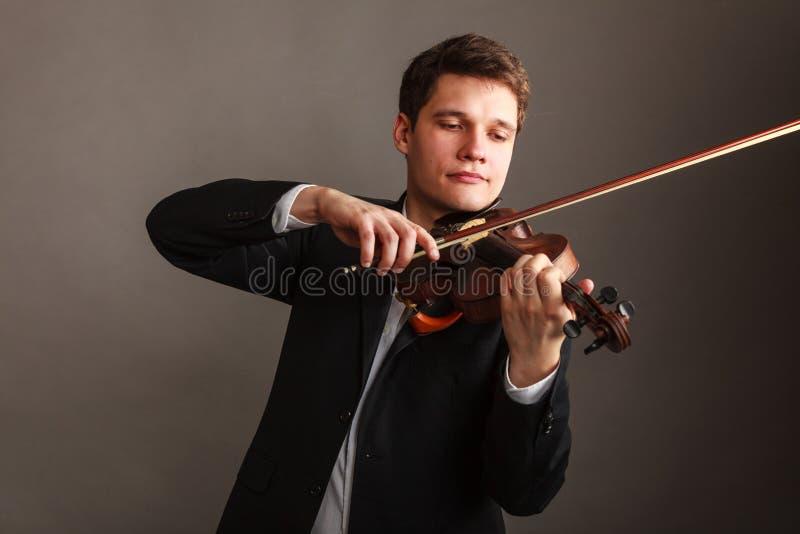 Το άτομο ατόμων έντυσε το βιολί κομψά παιχνιδιού στοκ φωτογραφία με δικαίωμα ελεύθερης χρήσης