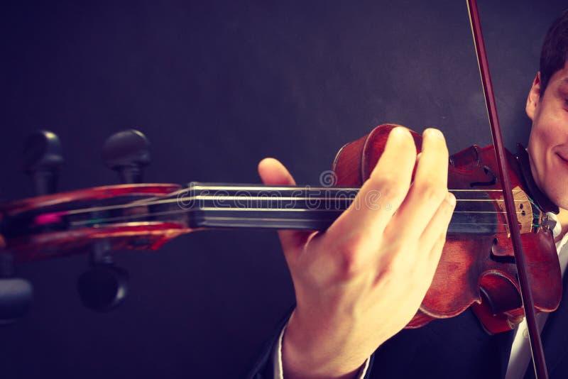 Το άτομο ατόμων έντυσε το βιολί κομψά παιχνιδιού στοκ φωτογραφίες