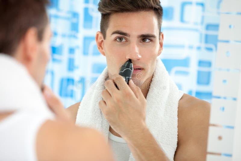 Το άτομο αφαιρεί την τρίχα από τη μύτη του στοκ εικόνες