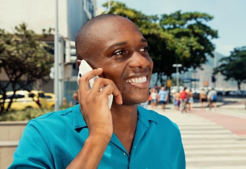 Το άτομο αφροαμερικάνων που χρησιμοποιεί το κινητό τηλέφωνο υπαίθριο σε έναν θερμό κινηματογράφο κοιτάζει στοκ φωτογραφία με δικαίωμα ελεύθερης χρήσης