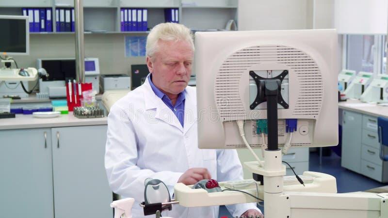 Το άτομο βάζει το χέρι του στον υπολογιστή στο εργαστήριο στοκ φωτογραφία