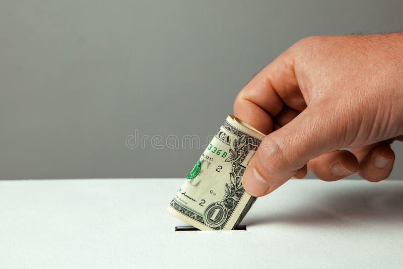 Το άτομο βάζει το χέρι του στο λογαριασμό δολαρίων στην αυλάκωση ενός κιβωτίου δωρεάς Διάστημα αντιγράφων για το κείμενο στοκ φωτογραφία με δικαίωμα ελεύθερης χρήσης