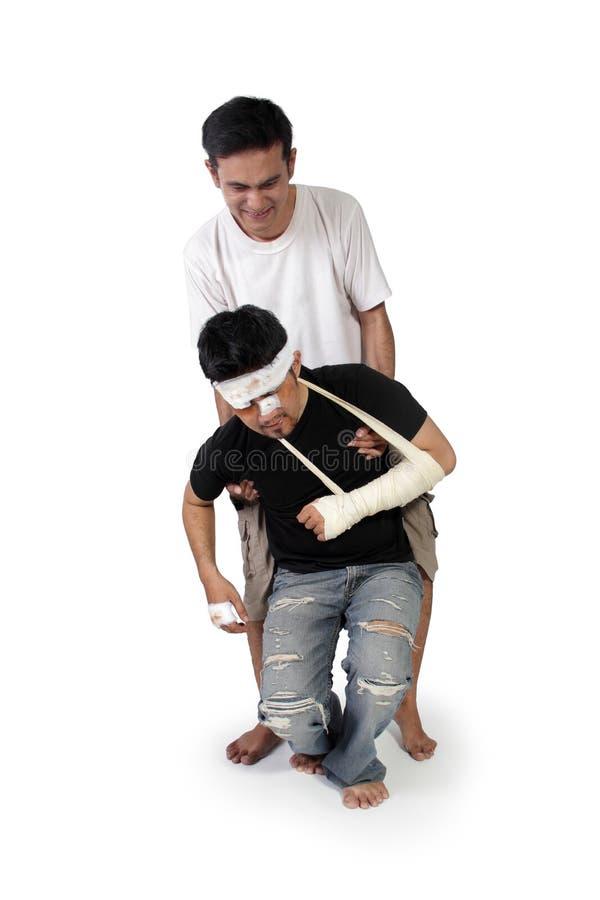 Το άτομο βοηθά το θύμα για να σταθεί επάνω στοκ εικόνα