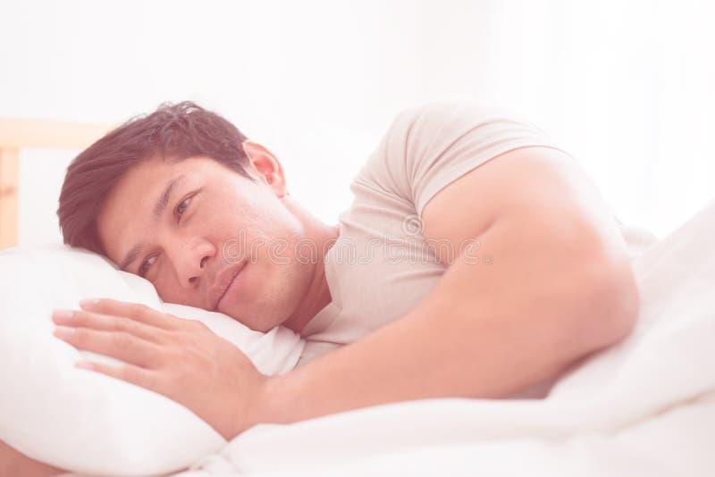 Το άτομο βρίσκεται αργά το πρωί στο κρεβάτι στοκ φωτογραφίες