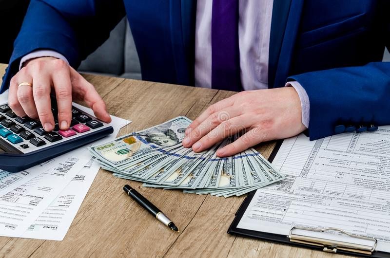 Το άτομο γεμίζει τη φορολογική μορφή, στοκ φωτογραφία με δικαίωμα ελεύθερης χρήσης