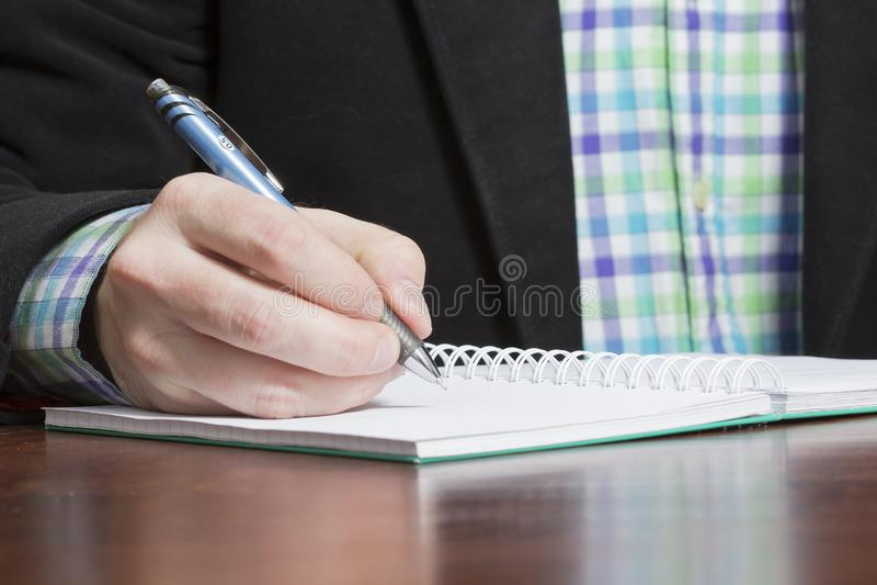 Το άτομο γράφει ένα υπόμνημα και φορά την επιχειρησιακή εξάρτηση στοκ εικόνα με δικαίωμα ελεύθερης χρήσης