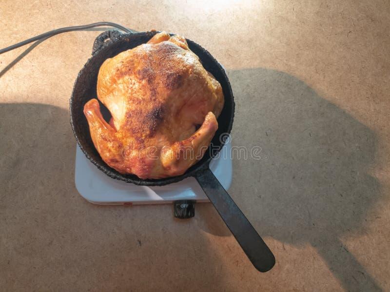 Το άτομο γυρίζει ένα τηγανισμένο κοτόπουλο σε ένα τηγάνι σε ένα hotplate Μαγειρεύοντας τηγανισμένο κοτόπουλο στοκ φωτογραφίες