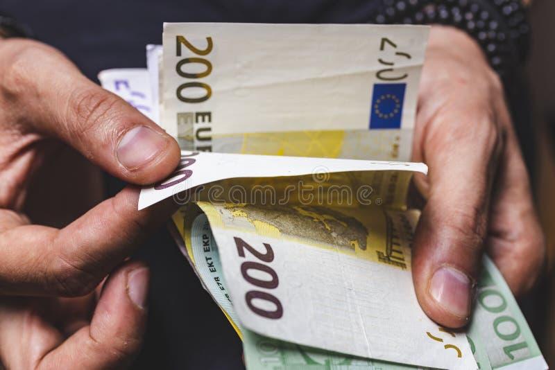 το άτομο δίνει τα μετρώντας τραπεζογραμμάτια μετρητών νομίσματος μεγάλου ποσού ευρο- στοκ εικόνα
