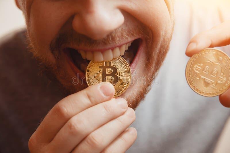 Το άτομο δαγκώνει ένα χρυσό νόμισμα με τα δόντια του στοκ εικόνα