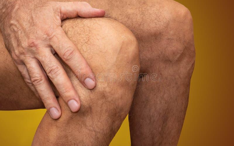 Το άτομο διατηρεί το γόνατο, ο πόνος στο γόνατο στοκ εικόνα