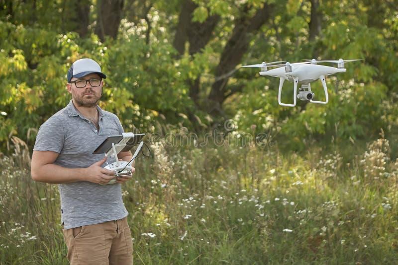 Το άτομο διαχειρίζεται τα quadrocopters Τηλεχειρισμός για τον κηφήνα στα χέρια των ατόμων εναέριο τηλεκατευθυνό&mu στοκ εικόνα