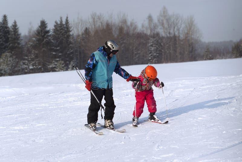 Το άτομο διδάσκει ένα παιδί που κάνει σκι χιονώδες mountainside στοκ εικόνες