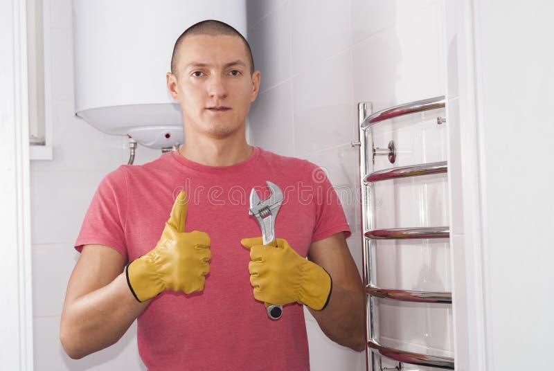 Το άτομο εγκαθιστά το στεγνωτήρα πετσετών στοκ φωτογραφία με δικαίωμα ελεύθερης χρήσης