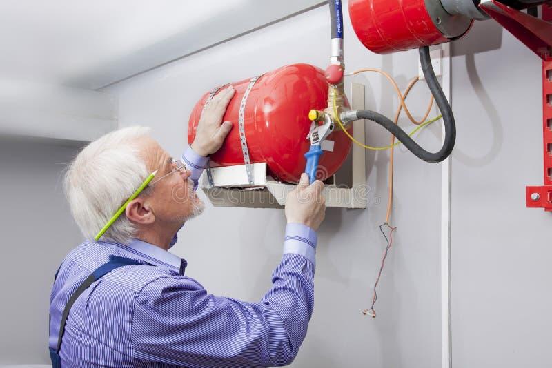 Το άτομο εγκαθιστά τον πυροσβεστήρα στοκ φωτογραφία με δικαίωμα ελεύθερης χρήσης