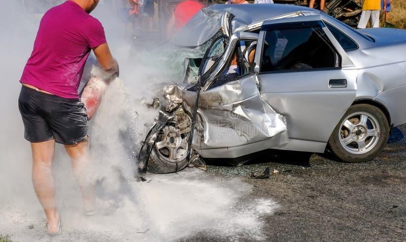 Το άτομο εξαφανίζει το αυτοκίνητο με έναν πυροσβεστήρα Χαλασμένος vehic στοκ φωτογραφία