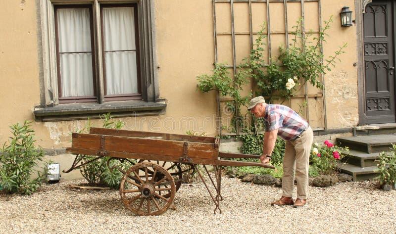 Το άτομο εξετάζει μια παλαιά χειράμαξα στοκ φωτογραφία