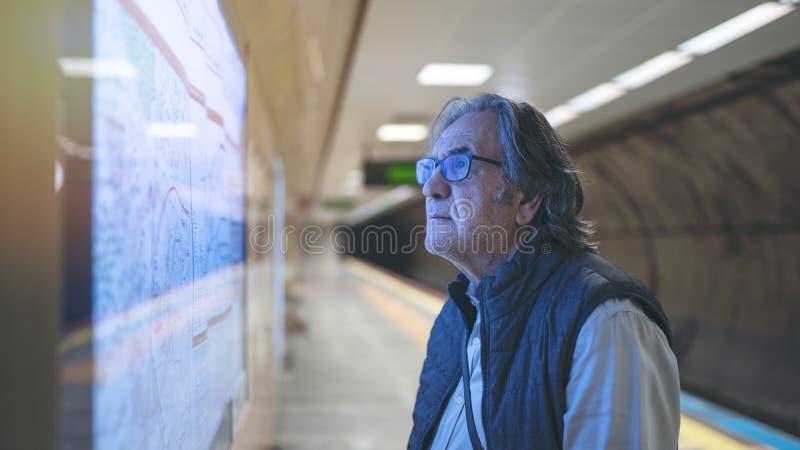 Το άτομο εξετάζει το χάρτη στο σταθμό τρένου μετρό στοκ φωτογραφία με δικαίωμα ελεύθερης χρήσης