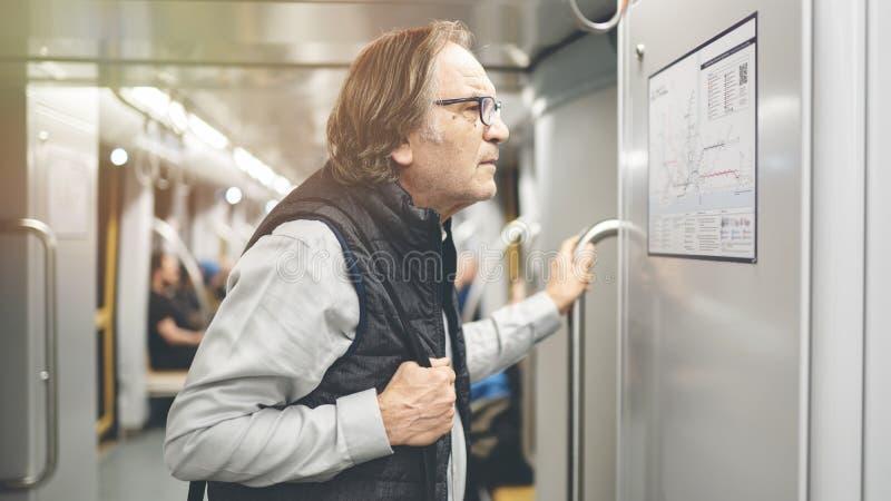 Το άτομο εξετάζει το χάρτη στο τραίνο μετρό στοκ εικόνα