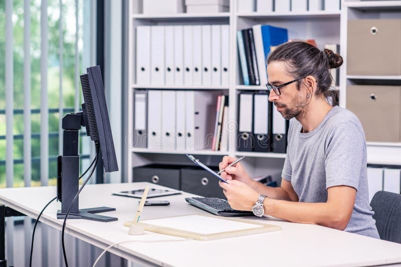 Το άτομο εργάζεται στο γραφείο του στοκ εικόνες