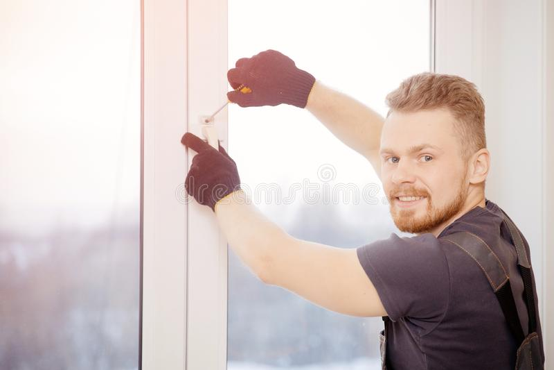 Το άτομο εργαζομένων εγκαθιστά τα πλαστικές παράθυρα και τις πόρτες με το διπλός-βερνικωμένο λευκό στοκ εικόνα με δικαίωμα ελεύθερης χρήσης