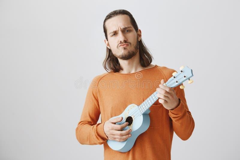 Το άτομο θα σας λικνίσει με την ικανότητα μουσικών του Πορτρέτο του βέβαιου όμορφου τύπου στην πορτοκαλιά εκμετάλλευση πουλόβερ u στοκ φωτογραφίες