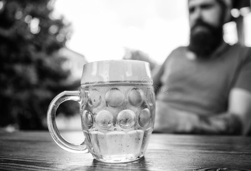 Το άτομο κάθεται το πεζούλι καφέδων απολαμβάνοντας την μπύρα Έννοια οινοπνεύματος και φραγμών Δημιουργικός νέος ζυθοποιός Η μπύρα στοκ εικόνες με δικαίωμα ελεύθερης χρήσης