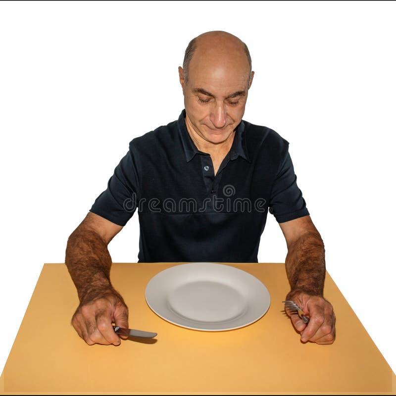 Το άτομο κάθεται στον πίνακα και εξετάζει το κενό πιάτο στοκ φωτογραφία με δικαίωμα ελεύθερης χρήσης