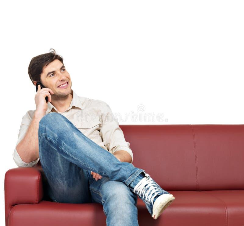 Το άτομο κάθεται στο ντιβάνι και μιλά στο κινητό τηλέφωνο στοκ φωτογραφία