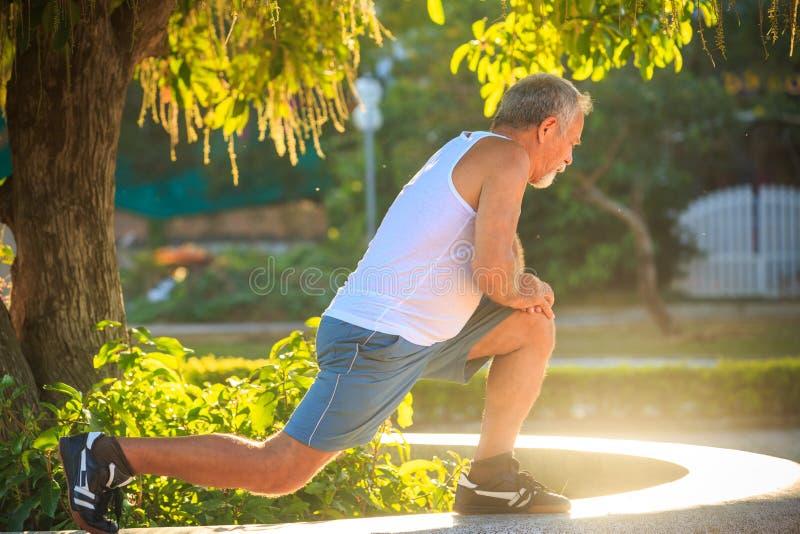 Το άτομο κάνει τις στάσεις οκλαδόν ασκήσεων πρωινού στο γόνατο στο πέτρινο εμπόδιο στοκ εικόνες με δικαίωμα ελεύθερης χρήσης