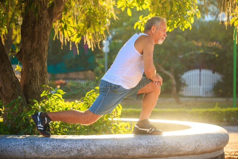 Το άτομο κάνει τις στάσεις οκλαδόν ασκήσεων πρωινού στο γόνατο στο πέτρινο εμπόδιο στοκ εικόνες
