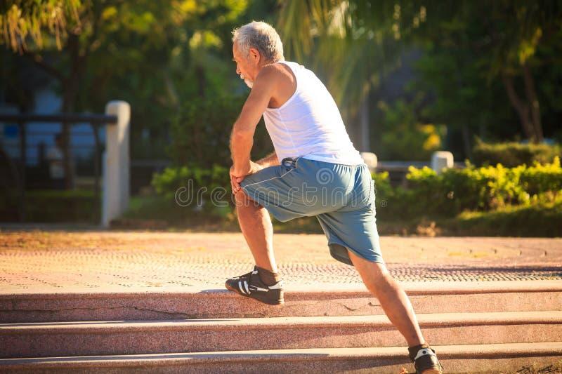 Το άτομο κάνει τις στάσεις οκλαδόν ασκήσεων πρωινού στο γόνατο στα πέτρινα βήματα στοκ φωτογραφίες