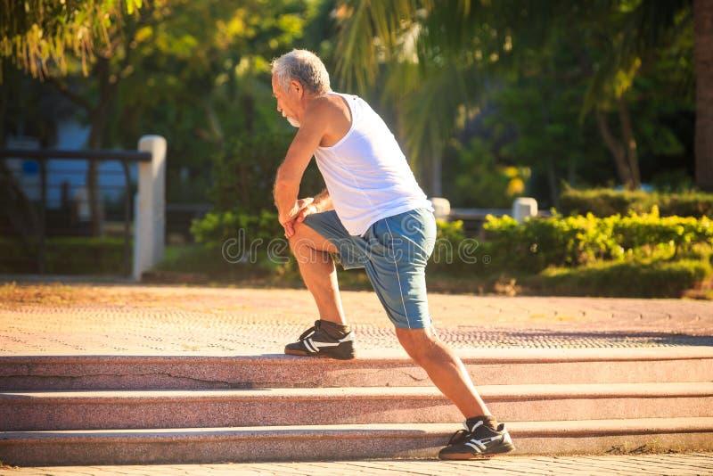 Το άτομο κάνει τις στάσεις οκλαδόν ασκήσεων πρωινού στο γόνατο στα πέτρινα βήματα στοκ εικόνα με δικαίωμα ελεύθερης χρήσης