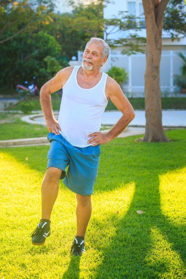Το άτομο κάνει τις στάσεις οκλαδόν ασκήσεων πρωινού στο δεξί γόνατο στη χλόη στοκ εικόνες με δικαίωμα ελεύθερης χρήσης