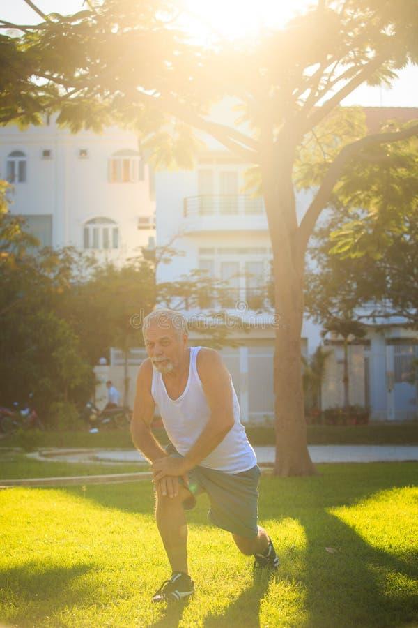 Το άτομο κάνει τις στάσεις οκλαδόν ασκήσεων πρωινού στο δεξί γόνατο στη χλόη στοκ εικόνα