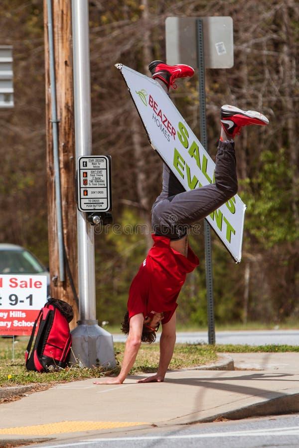 Το άτομο κάνει Cartwheel με το σημάδι για να προωθήσει το γεγονός εγχώριας αγοράς στοκ εικόνα με δικαίωμα ελεύθερης χρήσης